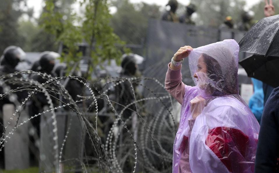 Una mujer está parada junto a un alambre de púas frente a la policía en el Palacio de la Independencia, la residencia del presidente Alexander Lukashe