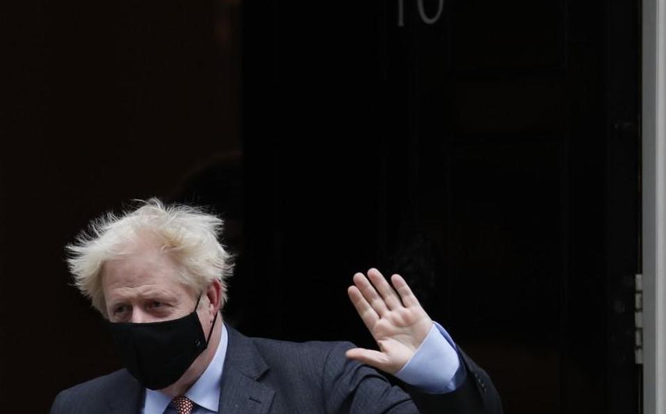 El primer ministro británico, Boris Johnson, saluda a los medios de comunicación mientras parte del número 10 de Downing Street para asistir a la Cáma